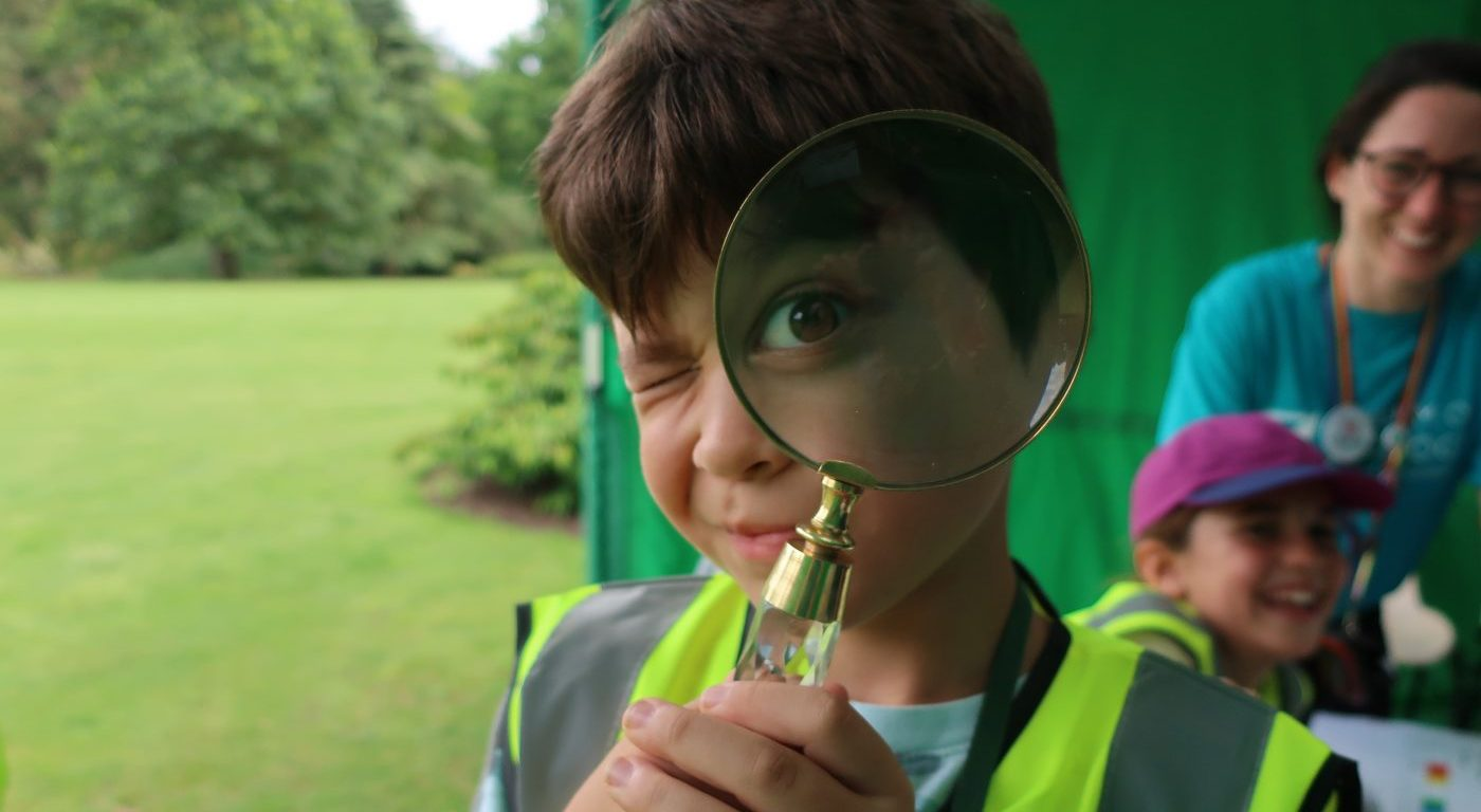 Boy looking through magnifyglass at camera
