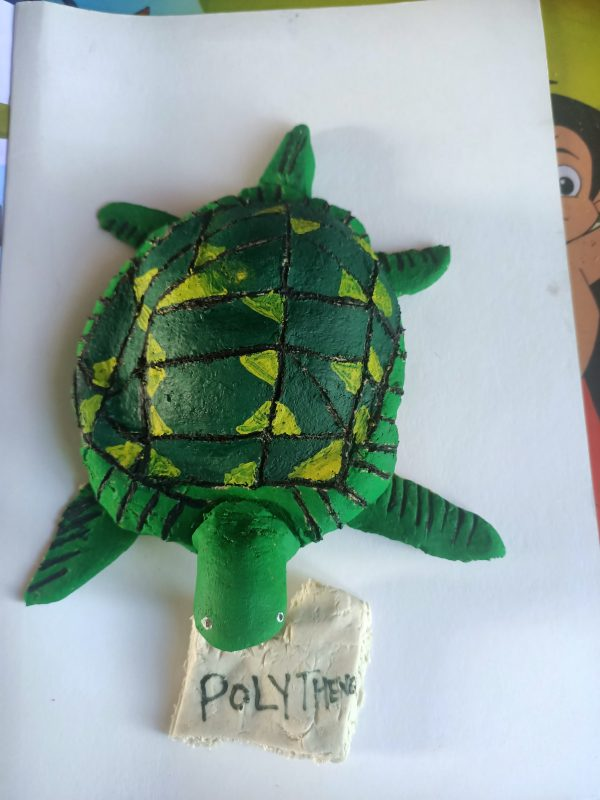 Salt dough sculpture or a green turtle with a bag in its mouth. The bag has 'polythene' written on it