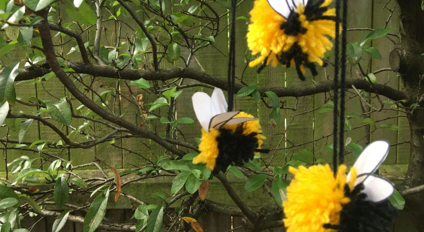 Yellow and black pom poms hanging in front of tree